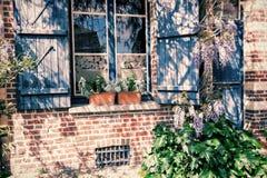 与蓝色快门的老房子窗口 库存照片