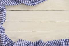与蓝色方格的桌布的白色木背景 免版税库存图片