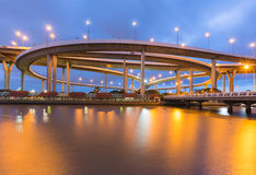与蓝色暮色天空的圆的交叉点高速公路水前面 免版税库存照片