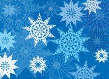 与蓝色有花边的雪花的背景 免版税库存照片