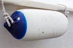 与蓝色条纹的白色小船防御者 库存图片