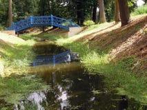与蓝色桥梁的小河 库存照片