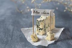 与蓝色模子的与名字的青纹干酪和横幅在灰色背景 复制空间 免版税库存照片