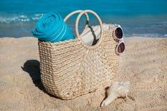 与蓝色毛巾的秸杆在热带沙子的袋子和太阳镜靠岸 图库摄影