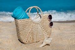 与蓝色毛巾的秸杆在热带沙子的袋子和太阳镜靠岸 免版税库存图片