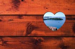 与蓝色海、绿色海岛和沿海城市的心形的孔在棕色木墙壁 图库摄影