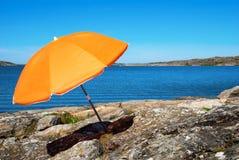 与蓝色海和橙色遮阳伞的瑞典海岸 库存照片