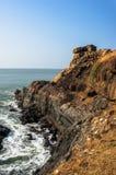 与蓝色海的陡峭的岩石碰撞在岩石的海岸和波浪 印度 图库摄影
