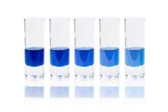 与蓝色液体的六块玻璃 免版税库存图片