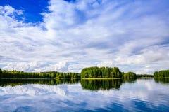 与蓝色湖和天空的田园诗乡下视图 夏天风景在农村芬兰 图库摄影