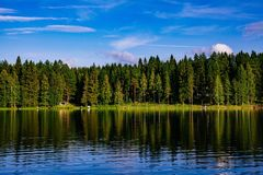 与蓝色湖和房子的田园诗乡下风景视图岸的 村庄芬兰夏天 库存照片