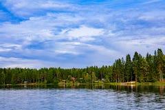 与蓝色湖和房子的田园诗乡下风景视图岸的 村庄芬兰夏天 库存图片
