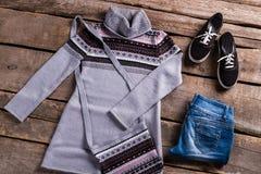 与蓝色牛仔裤的灰色长袍 库存照片