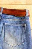 与蓝色牛仔裤的静物画在木背景 库存照片