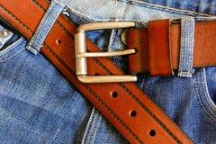 与蓝色牛仔裤的静物画在木背景 免版税库存照片