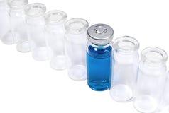 与蓝色疫苗的小玻璃瓶在空的flacons行  免版税库存照片