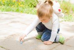 与蓝色白垩的逗人喜爱的小女孩图画 免版税库存图片