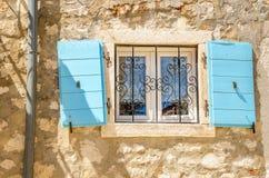与蓝色的美丽如画的窗口关闭白色石灰石墙壁克罗地亚,巴尔干 免版税库存图片
