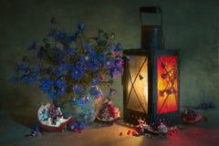 与蓝色矢车菊花束的静物画在一个老土制瓶子、一个被点燃的古色古香的灯笼,以及片断的残破明亮 库存图片
