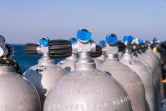 与蓝色磁带和海的佩戴水肺的潜水坦克在背景中 库存照片