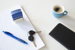 与蓝色笔、邮票、智能手机和咖啡的被排行的纸在白色书桌上 免版税库存图片