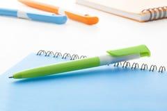 与蓝色笔记本的绿色塑料圆珠笔 库存图片