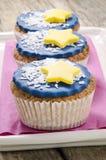 与蓝色结冰和黄色星形的杯形蛋糕 免版税库存照片