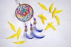 与蓝色羽毛的Dreamcatcher在黄色向日葵petalson之间木背景 图库摄影