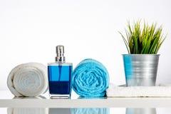 与蓝色肥皂分配器的装饰的白色浴 免版税库存图片