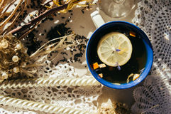 与蓝色花、橙皮和瓣的红茶在蓝色和 免版税库存图片