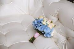 与蓝色花的婚礼花束在白色背景 图库摄影
