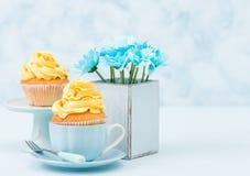 与蓝色菊花嫩黄色奶油色装饰和花束的杯形蛋糕在减速火箭的破旧的别致的花瓶的在蓝色淡色背景 免版税库存照片
