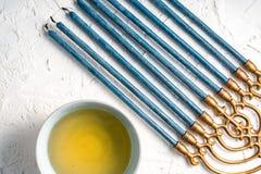 与蓝色蜡烛和黄油的黄铜Hanukiya Menorah在碗对角线 图库摄影