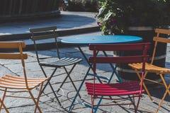 与蓝色表夏令时Instagram接触的四把五颜六色的椅子 库存照片