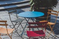 与蓝色表夏令时Instagram接触的四把五颜六色的椅子 免版税库存照片