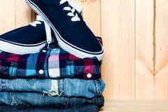 与蓝色运动鞋、衬衣和牛仔裤的静物画在木背景,偶然人 库存图片