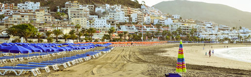 与蓝色遮阳伞和sunbeds, Los Cristianos, Tene的沙滩 免版税图库摄影