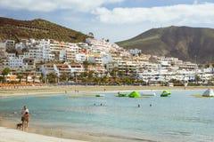 与蓝色遮阳伞和sunbeds, Los Cristianos, Tene的沙滩 免版税库存照片