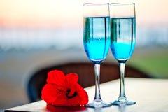 与蓝色酒精鸡尾酒的二块玻璃与一朵异乎寻常的花 免版税库存图片