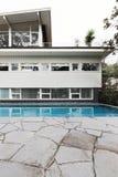 与蓝色铺磁砖的游泳池和craz的中世纪家庭外部 免版税图库摄影