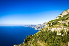 与蓝色陆间海,阿马飞海岸的意大利岩石海岸线 免版税库存图片