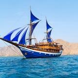 与蓝色风帆的葡萄酒木船 库存照片