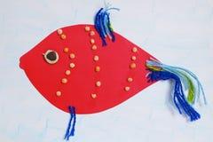 与蓝色飞翅的儿童` s补花红色鱼 免版税库存照片