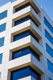 白色大理石大厦的角落与蓝色玻璃Windows的 免版税库存照片