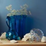 与蓝色玻璃花瓶和贝壳的静物画 免版税图库摄影