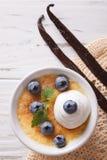 与蓝莓特写镜头的焦糖奶油点心 垂直的顶视图 免版税图库摄影