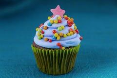 与蓝莓结霜的杯形蛋糕和五颜六色洒 免版税库存图片