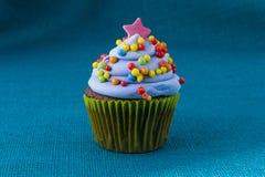 与蓝莓结霜的杯形蛋糕和五颜六色洒 图库摄影