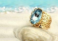 与蓝绿色的Jewellry圆环在夏天沙子海滩 免版税库存照片