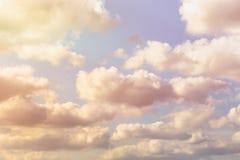 与蓬松云彩的抽象天空背景在温暖的口气和阳光作用 免版税库存图片